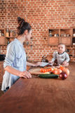 Young mother with her little son cooking dinner together and using digital tablet in the kitchen Royalty Free Stock Images