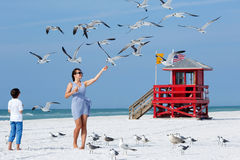 Young mother and her little son feeding seagulls on tropical beach Royalty Free Stock Photography