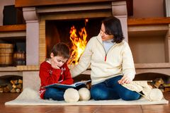 Mother and her little son by a fireplace at home Royalty Free Stock Photo
