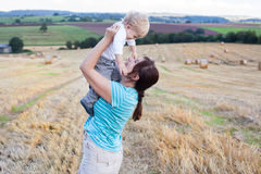 Young mother and her little son having fun in straw field Stock Photography