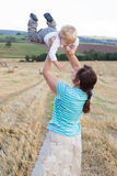 Young mother and her little son having fun in straw field Royalty Free Stock Photography