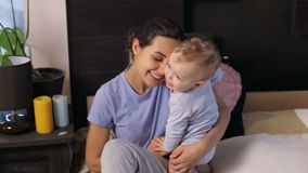 Young mother with her little son are relaxing and playing in the bedroom. Young mother with her one years old little son dressed in pajamas are relaxing and stock video footage
