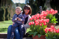 Young mother and her little son in a tulip garden Stock Photos