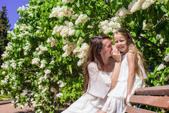 Young mother and her lovely daughter whispering on Stock Images