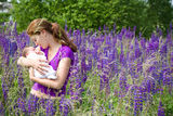 Young mother with her newborn baby in field. Young mother with her newborn baby in purple lupines field Stock Photos