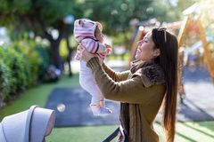 Young mother with her newborn baby at a playground in the park stock photos