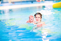 Young mother and her newborn baby swimming Royalty Free Stock Images
