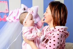Young mother hugs her little daughter in the room Royalty Free Stock Photography