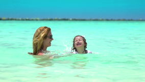 A young mother with her small daughter playing in the turquoise waves of the sea. Slow motion stock video