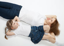 Young mother and her smiling little daughter lying on the floor Stock Photos