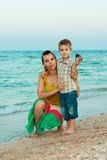 Young mother with her son on the beach with shell Stock Photos
