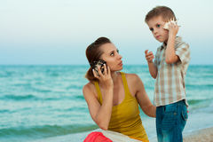 Young mother with her son on the beach with shells Stock Photo