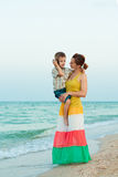 Young mother with her son on the beach with shells Royalty Free Stock Photo