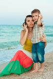 Young mother with her son on the beach with shells. Royalty Free Stock Photos