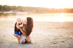 Young mother with her son on the beach on a sunset background. Unplugged mindfull Stock Images