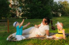 A young mother with her son and daughter lie on the grass and are happy with soap bubbles stock image