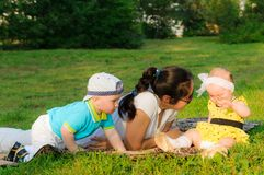 Young mother with her son and daughter lie on the grass stock images