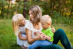 Young mother and her son and daughter together playing. Family outdoors, mother and her son and daughter together playing Stock Photo