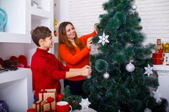 A young mother and her son decorate the Christmas tree at home. Merry Christmas and Happy Holidays Royalty Free Stock Image