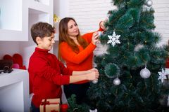 A young mother and her son decorate the Christmas tree at home. Merry Christmas and Happy Holidays Stock Photos