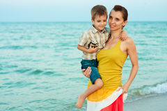 Young mother with her son goes on the beach Royalty Free Stock Image