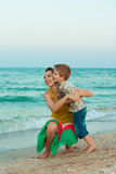 Young mother with her son having fun on the beach. Family portrait. Young mother with her son having fun on the beach Stock Images