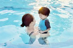 Young mother and her son having fun in a swimming pool. At sunset Stock Photography
