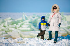 Young mother and her son on icy beach Stock Photography
