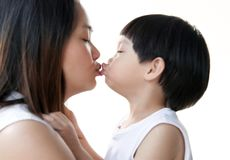 Young mother and her son kissing together on whit. Young asian mother and her son kissing together on white background : Close up stock images