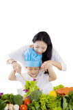 Young mother and her son mixing a salad. Portrait of young mother and her son mixing a salad in the studio, isolated on white background Stock Image