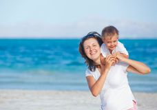 Young mother and her son playing at beach Stock Photography