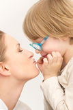 Young mother with her son playing and kissing each other. Smiling portrait of family Stock Photos