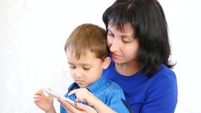 Young mother and her son playing smartphone and smiling, on white background stock video footage