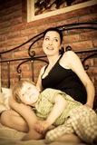 Young mother with her son relaxing on the bed. Young mother with her child son relaxing on the bed against brick wall background focus on mother Stock Images