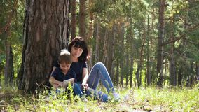 A young mother and her son are relaxing in the park, sitting by a tree and using a gadget. Contemporary technology. stock video