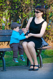 Young mother and her son sitting on bench Royalty Free Stock Photography