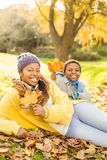 Young mother with her son sitting in leaves. On an autumns day Royalty Free Stock Image