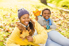 Young mother with her son sitting in leaves Royalty Free Stock Photography