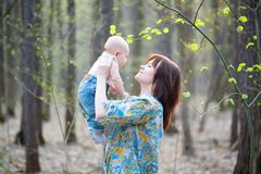 Young mother with her son in a spring forest Stock Images