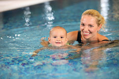 Young mother and her son in a swimming pool. Young cheerful mother and little son enjoying swimming in a swimming pool royalty free stock image