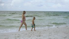 Young mother and her son are walking on the beach along the seashore USA 4k stock footage