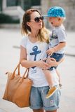 Young mother and her son walking in city Royalty Free Stock Photography