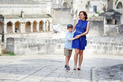 Young mother and her son walking outdoors in city Stock Image