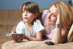 Young mother with her son watch tv. Happy and surprised by something Stock Images