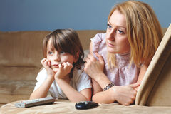 Young mother with her son watch tv, sad face Stock Photo