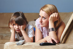 Young mother with her son watch tv, sad face. Young mother watch tv with her son, sad and serious face expression Royalty Free Stock Image