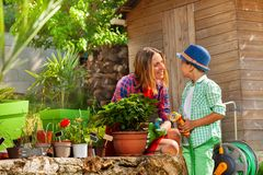 Young mother and her son watering plants outdoors royalty free stock photo