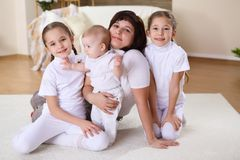 A young mother with her three daughters at home Royalty Free Stock Images