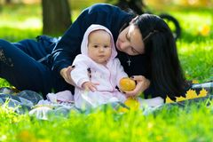 Young mother with her tiny baby in a park. royalty free stock photo