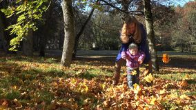 Young mother and her toddler girl have fun in autumn nature. 4K stock footage